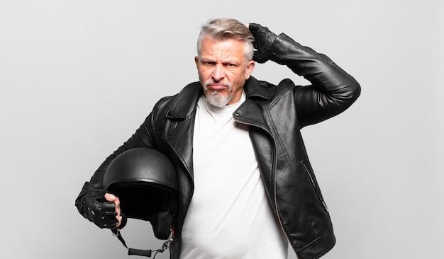 어리둥절하고 혼란스러워 머리를 긁적이며 옆을 바라보는 수석 오토바이 라이더