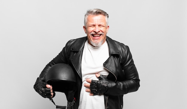 Старший наездник на мотоцикле громко смеется над какой-то веселой шуткой, чувствует себя счастливым и веселым, веселится