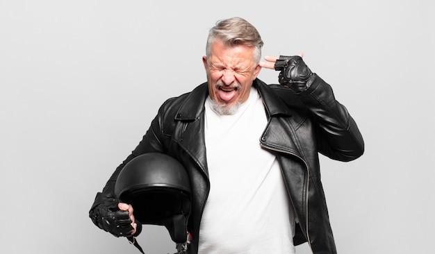 Старший мотоциклист выглядит несчастным и подчеркнутым, жест самоубийцы делает знак пистолетом рукой, указывая на голову