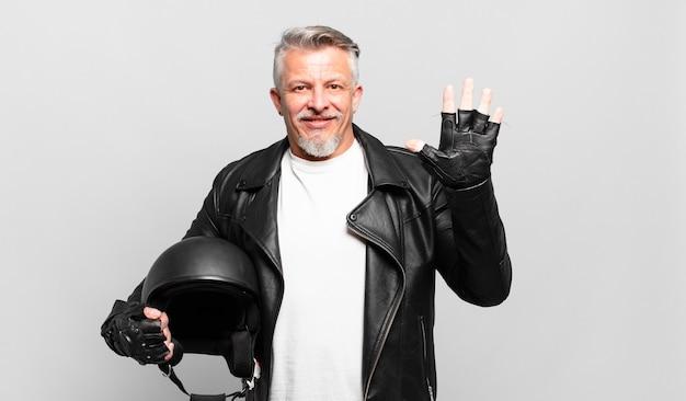 Старший мотоциклист улыбается и выглядит дружелюбно, показывает пятый или пятый номер рукой вперед и ведет обратный отсчет