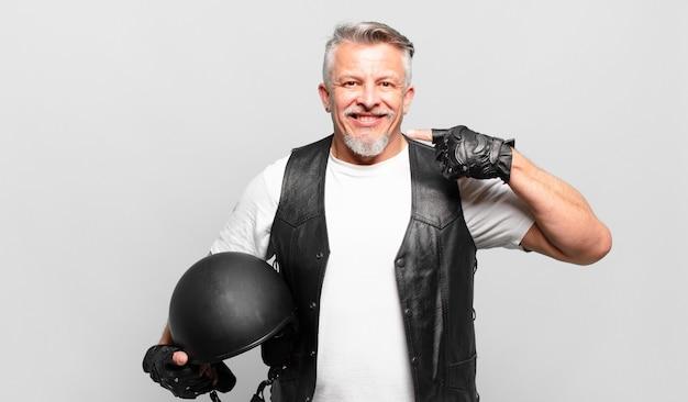 Старший мотоциклист, уверенно улыбаясь, указывая на собственную широкую улыбку, позитивное, расслабленное, удовлетворенное отношение