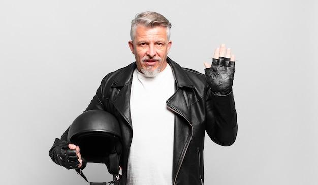 Старший мотоциклист радостно и весело улыбается, машет рукой, приветствует и приветствует вас или прощается