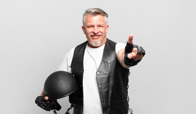 Старший мотоциклист, гордо и уверенно улыбаясь, триумфально принимает позу номер один, чувствуя себя лидером
