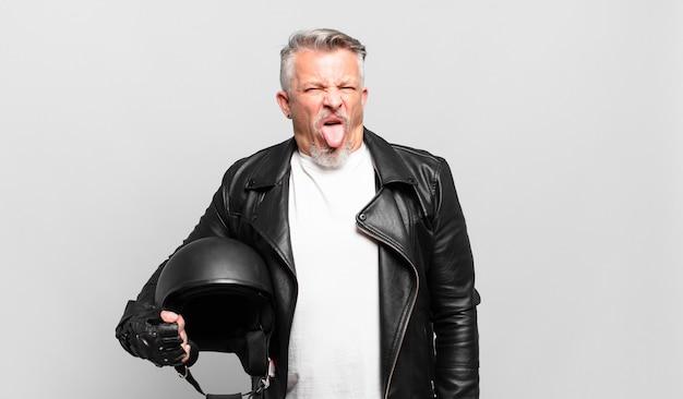 Senior motorbike rider with cheerful, carefree, rebellious attitude, joking and sticking tongue out, having fun