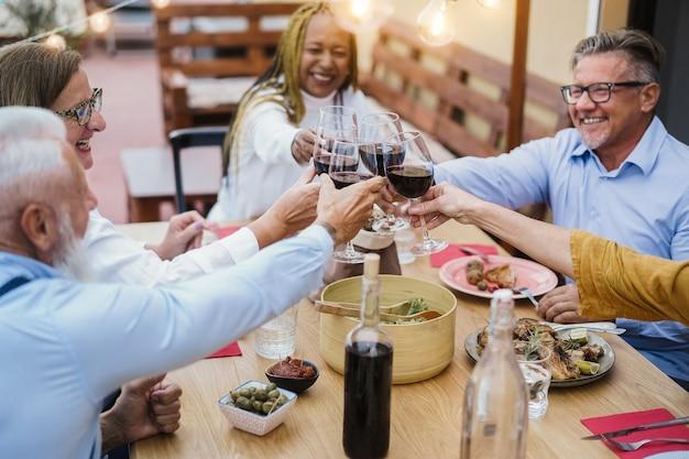 Старшие многорасовые люди веселятся, подбадриваясь с вином за ужином в патио - сосредоточьтесь на руках, держащих очки