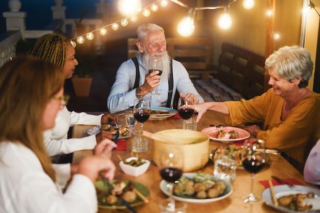 Senior multiracial people having fun in dinner at patio