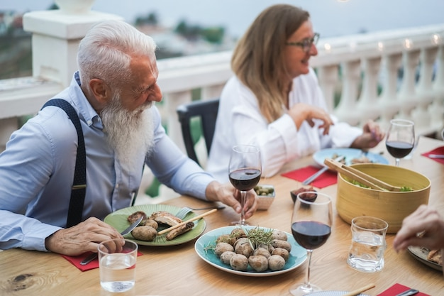 Senior multiracial people having fun drinking wine at patio dinner - focus on left senior man hand
