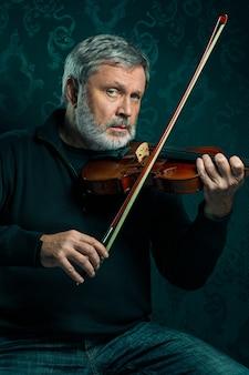 Старший музыкант играет на скрипке с палочкой на черном