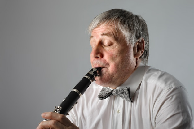 Senior musician playing on a clarinet
