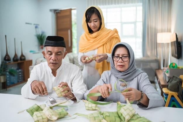 Старшая мусульманская пара и дочь делают кетупат для празднования ид фитр мубарак дома Premium Фотографии