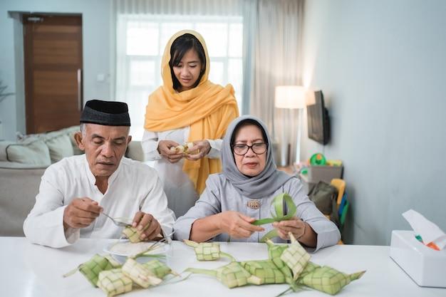 为eid fitr穆巴拉克庆祝的资深穆斯林夫妇和女儿做Ketupat在家