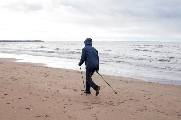 海の近くの屋外で素敵な秋の日を楽しんでいるシニア北欧ポールウォーカー。アクティブな老人と女性