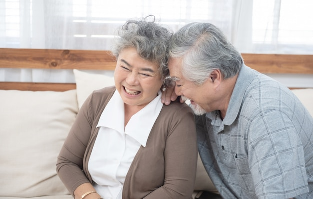 Senior old asian couple laugh sit on sofa at home.