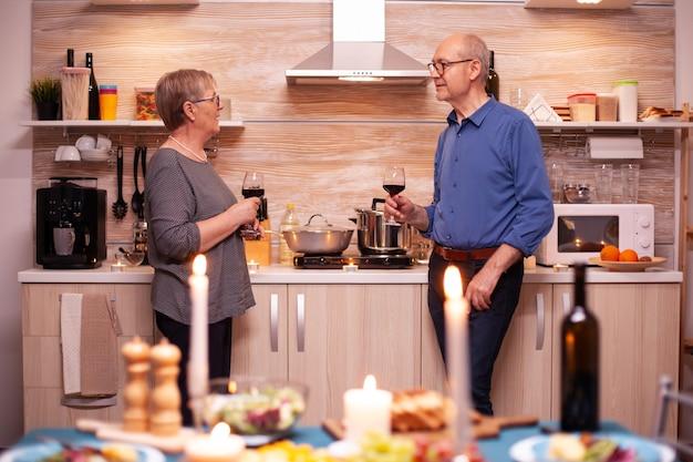 キッチンでロマンチックなディナー中にワインを飲みながらおしゃべりをしている年配の老夫婦。健康的な食事の間に楽しい会話をして話すのが大好きな老夫婦。