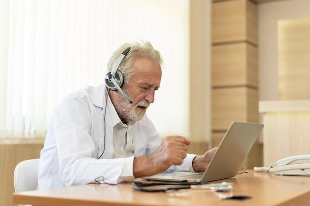 Старший старый врач носит наушники. дистанционная медицинская консультация в чате, дистанционные услуги телемедицины. концепция телездравоохранения