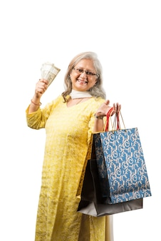 Senior or old indian or asian lady with shopping bags and money fan, standing isolated over white background