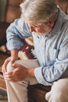 Senior old man facing knee problem, sitting on sofa holding knee at home. elderly man suffering from severe knee ache sitting in living room. elderly man grabbing his knee in pain