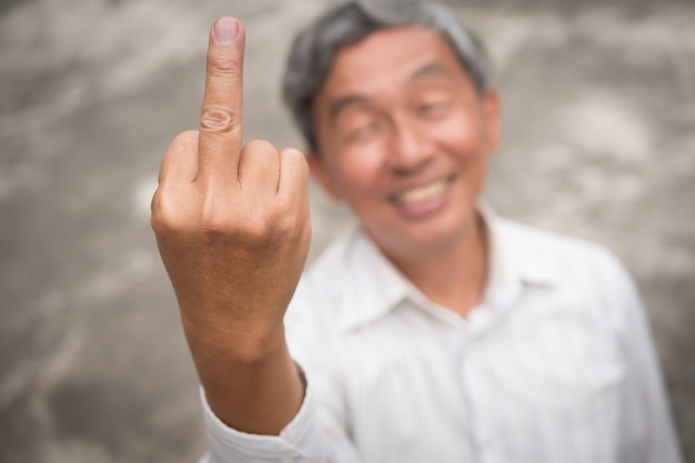 Senior old man flipping middle finger