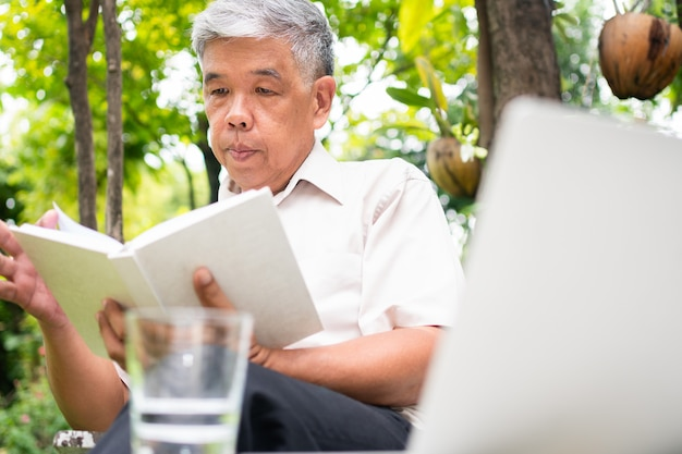 Старший старик читает книгу в парке и пьет воду. понятие пенсионного образа жизни и хобби.