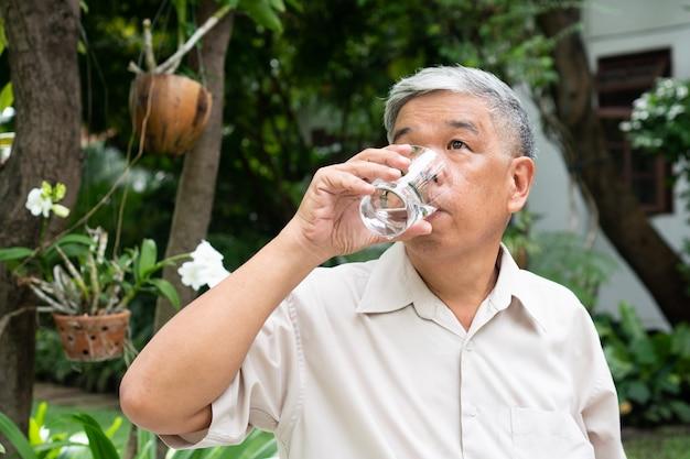 公園で本を読んで水を飲む年配の老人。