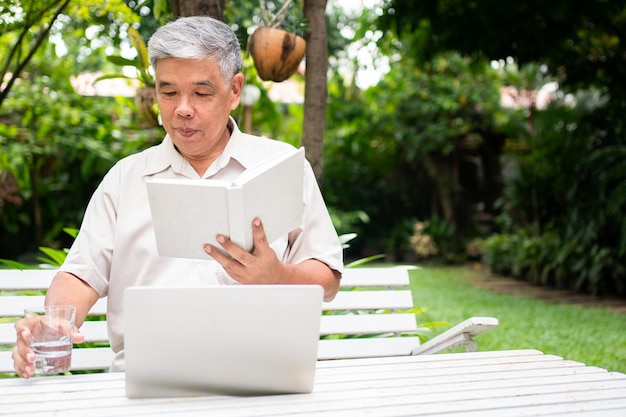 공원에서 책을 읽고, 물을 마시고 자신의 노트북을 사용하는 수석 노인