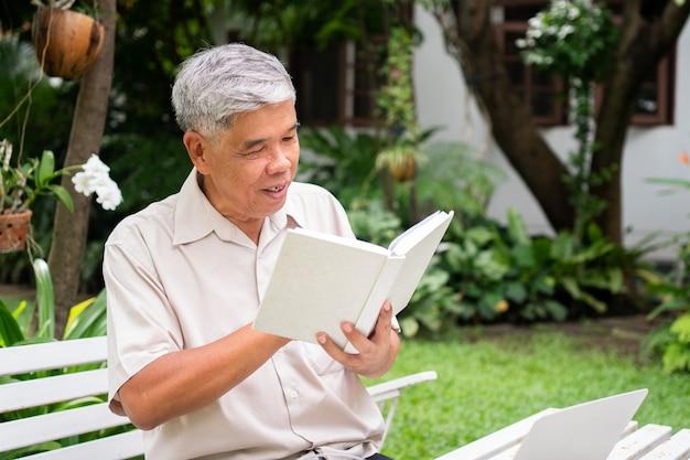 公園で本を読んでいる年配の老人。