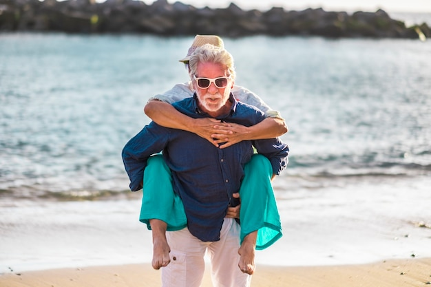 Senior old people couple have fun together at the beach in summer holiday vacation