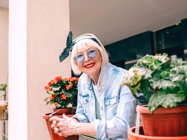 Старшая старая стильная женщина с седыми волосами и в синих очках и джинсовой ткани, стоящая на балконе на открытом воздухе