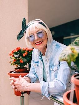 灰色の髪と青いメガネとデニムで屋外のバルコニーに立っている年配のスタイリッシュな女性