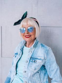세련된 머리띠와 파란색 안경을 쓴 회색 머리를 한 세련된 노부인