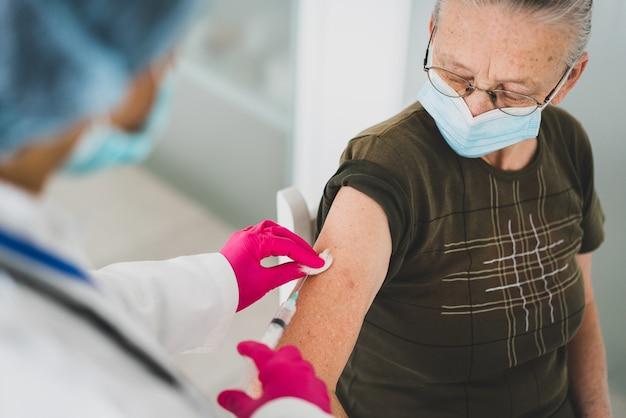 Старшая пожилая женщина в больнице получает вакцину