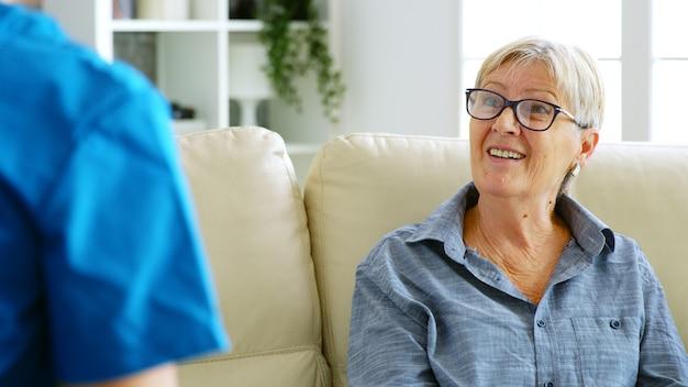 ナーシングホームのソファに座って医者と話している年配の老婆。肩越しのショット