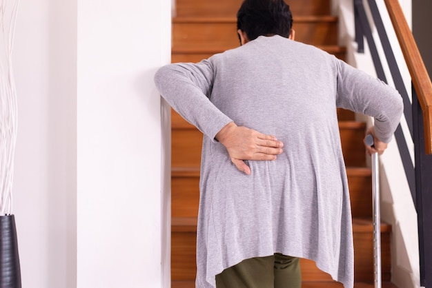 Senior older woman suffering from low-back lumbar pain while walking on stair at home,low back pain lumbar backache