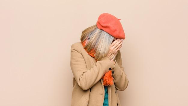Симпатичная женщина старшего или среднего возраста закрыла глаза руками с грустным, разочарованным взглядом отчаяния, плача, вид сбоку