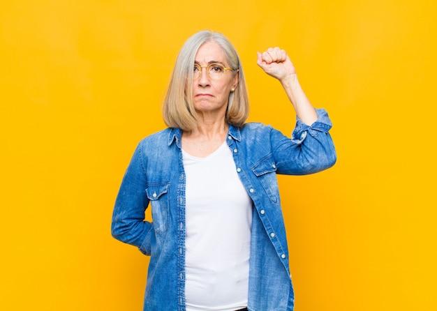 Симпатичная женщина старшего или среднего возраста чувствует себя серьезной, сильной и мятежной, поднимает кулак, протестует или борется за революцию