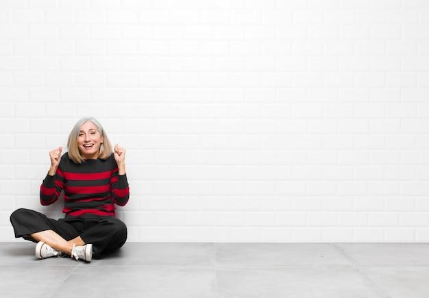 Женщина старшего или среднего возраста чувствует себя потрясенной, взволнованной и счастливой, смеется и празднует успех, говоря: