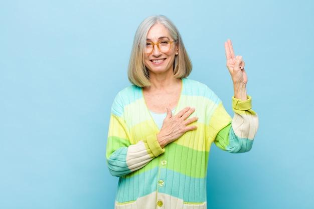 Женщина старшего или среднего возраста выглядит счастливой, уверенной и заслуживающей доверия, улыбается и показывает знак победы, с позитивным настроем