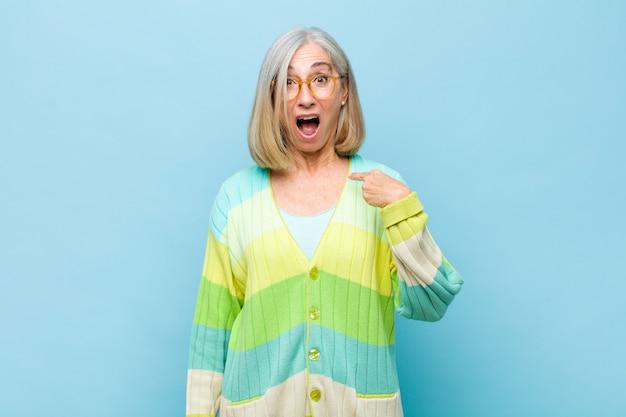 Женщина старшего или среднего возраста выглядит шокированной и удивленной с широко открытым ртом, указывая на себя