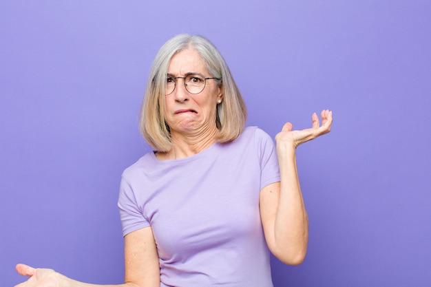 頭がおかしくて、頭がおかしくて、混乱して、困惑した表情で肩をすくめて、イライラして無知なシニアまたは中年の女性