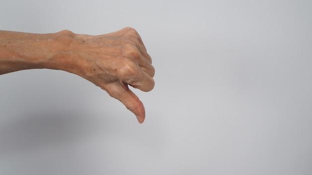 年配または年上の女性は、白い背景の上の手のサインを親指ダウンしています。何かが気に入らない、または承認しない場合に使用します。