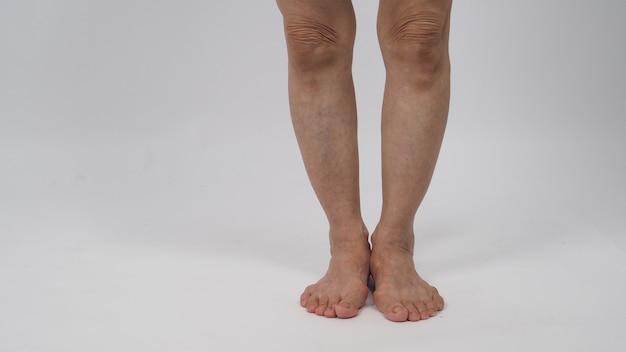 白い背景の上に裸足で立っている年配または年配の女性の脚。