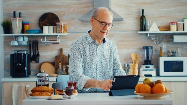 健康的なライフスタイルを持っている朝食時にキッチンでタブレットpcを閲覧しているシニアの親。モバイルアプリ、現代のインターネットオンライン情報を使用して定年のタブレットポータブルパッドpcを持つ高齢者
