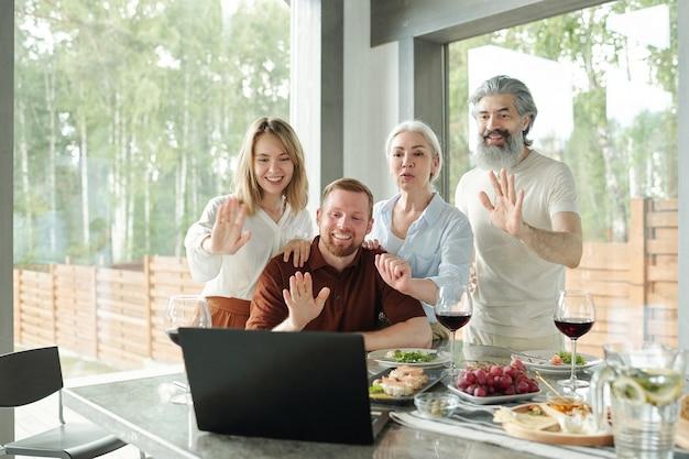 Старшие родители и их взрослые дети машут руками ноутбуку во время разговора с родственниками через приложение для видеоконференцсвязи