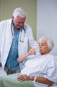 水のガラスを飲むシニアの患者