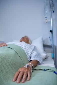Senior patient hand with saline on bed in hospital