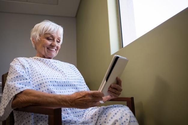 Старший пациент, держащий цифровой планшет