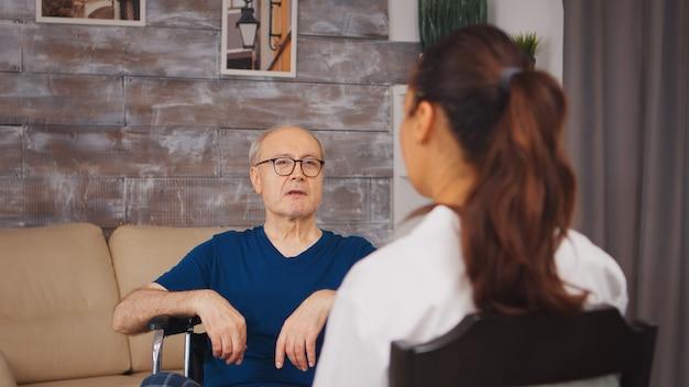 医療従事者と話している車椅子のシニア患者。ナーシングホーム支援、ヘルスケア、医療サービスの医療従事者を持つ障害者高齢者