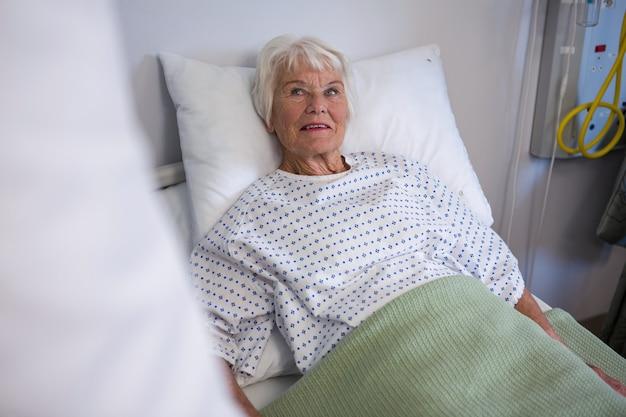 Старший пациент, лежа на кровати