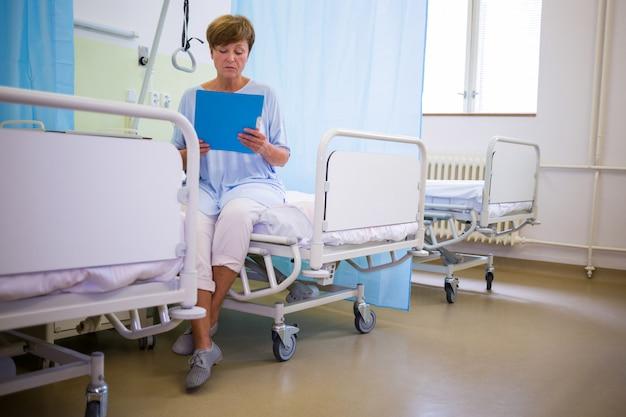 Старший пациент сидит на кровати с отчетом