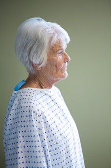Старший пациент, стоящий в больнице